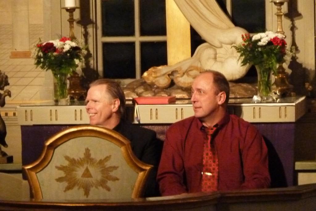 Lennart Raswill och Per Sundin har roligt sittande i altarringen under ett av numren på konserten.